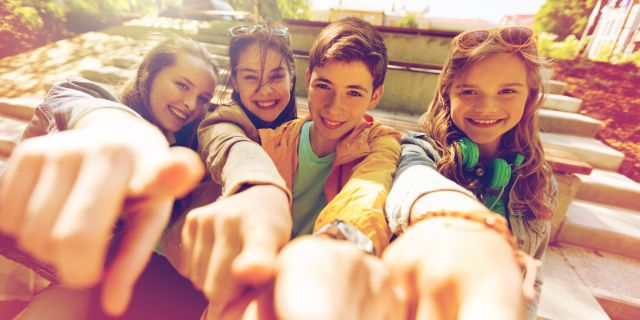 teenage friends or students pointing finger at you